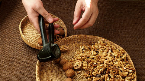 Woman hand is cracking a walnut with metal nutcracker GIF