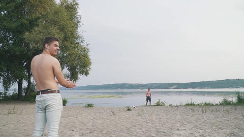Two guys playing with a soccer ball on the beach near the river Two friends Live Action