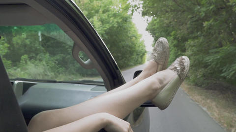 Female legs in the window of a car moving on the road Women's legs sticking out Live Action