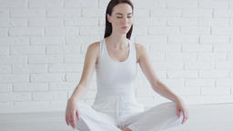 Young woman meditating in white room Archivo