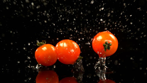 Tomatoes falling on water against black background 4k Live Action