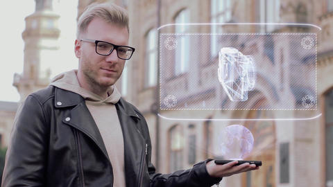Smart young man with glasses shows a conceptual hologram pocket camera Footage