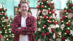Happy Young Man Smiling Against Illuminated Christmas Trees Outdoors Footage
