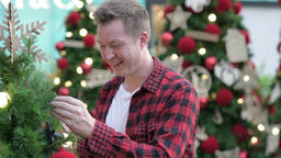Young Happy Hipster Man Smiling While Looking At Christmas Trees Outdoors Footage