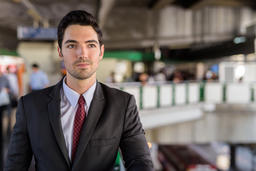Portrait of young handsome businessman wearing suit in city Photo