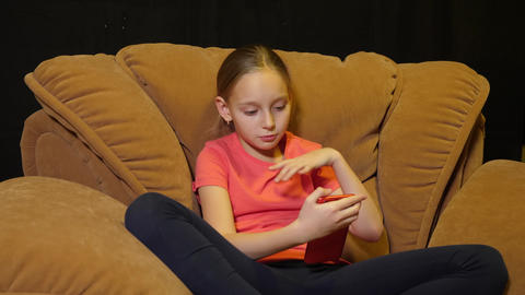 Young teenager girl sitting on cozy chair using mobile phone on black background ビデオ