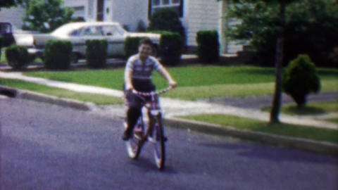 1961: Boy rides USA flag laden bike around suburban streets Footage