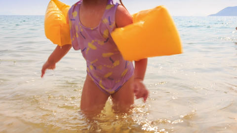 Closeup Little Girl in Armbands Goes out of Sea to Beach Live Action