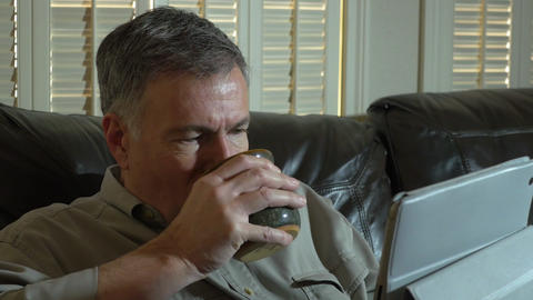 man drinking coffee while using a tablet pc Live Action