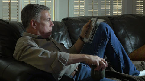 man relaxing on his couch drinking coffee using a tablet pc Footage