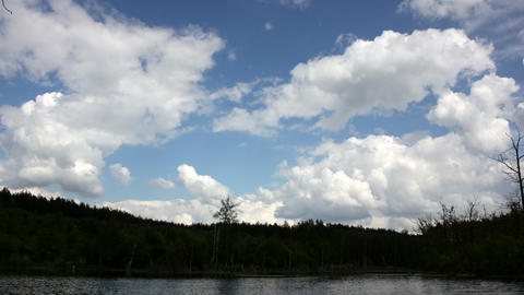 Blue sky, white clouds and green forest + lake timelapse (25 sec) Footage
