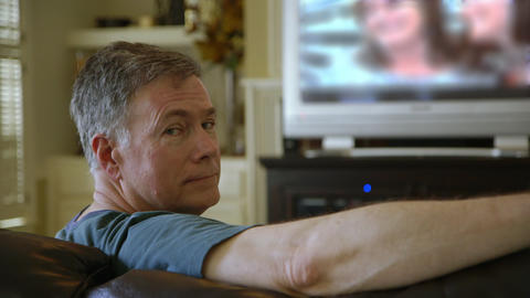 man sitting on couch watching TV turns around and smiles Footage