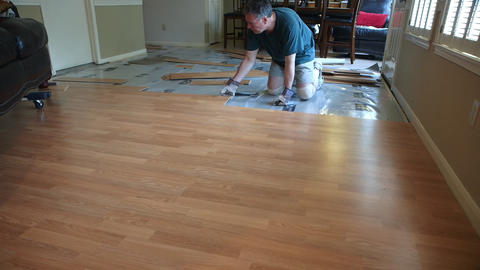 wide shot of workman removing laminate flooring Footage