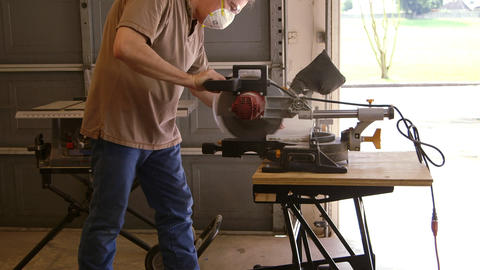 woodworker using a power miter saw to cut a board Footage