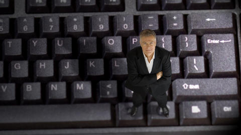 tiny businessman standing on a keyboard Footage