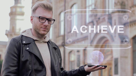 Smart young man with glasses shows a conceptual hologram Achieve Footage