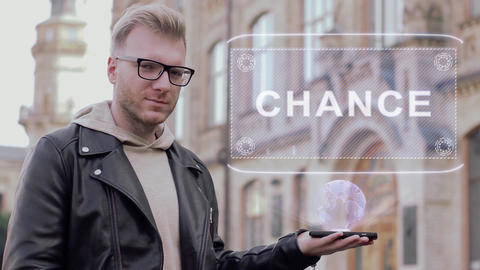 Smart young man with glasses shows a conceptual hologram Chance Live Action