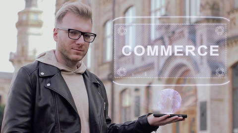Smart young man with glasses shows a conceptual hologram Commerce Live Action