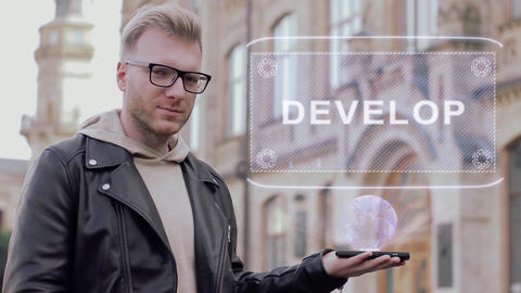 Smart young man with glasses shows a conceptual hologram Develop Live Action