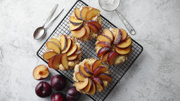 Homemade crumble tarts with fresh plum slices placed on iron baking grill Footage