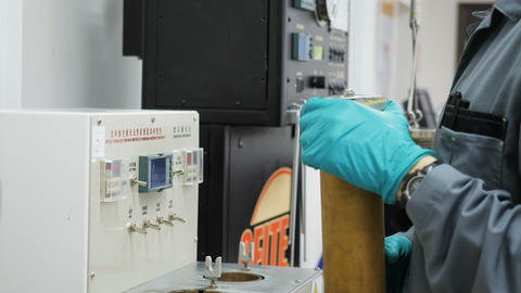 side view lab assistant puts cylinder into examine device Footage