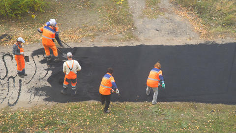 Construction workers during asphalting road. Manual labor… Stock Video Footage