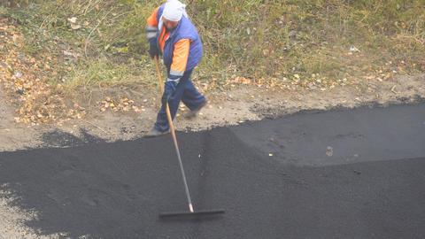 Female worker during asphalting road. Heavy female manual labor in construction Live Action