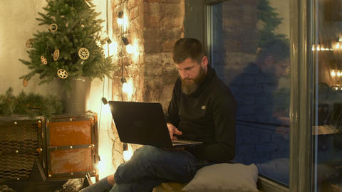 Male blogger with laptop sitting on windowsill Footage