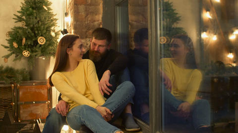 Relaxed chatting couple sitting on windowsill Footage