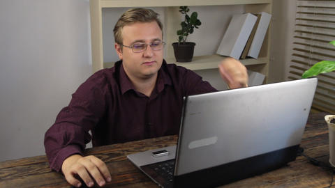 Tired businessman with eyeglasses in office near laptop Footage