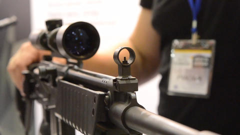 Weapon optics close-up with a man in the back blurred background Live Action