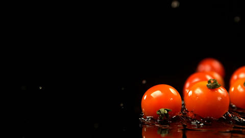 Tomatoes rolling on water against black background 4k Live Action