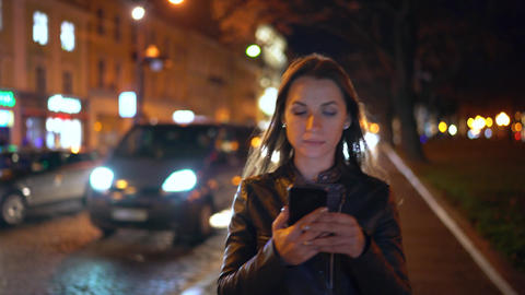 Attractive woman uses a smartphone while walking through the streets of the Archivo