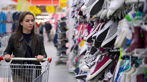 Woman chooses sports or home shoes in the supermarket Live Action
