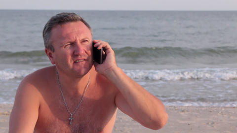 Smiling man talking by phone on a beach Footage