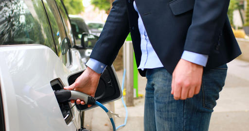 Businessman charging electric car at charging station 4k Live Action