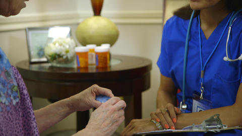 home healthcare nurse handing the pill box to her patient Live Action