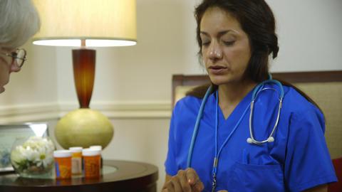 home healthcare nurse placing patients medicine in pill box Footage
