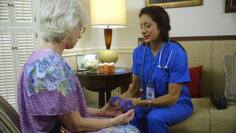 Home Healthcare Nurse Showing Her Patient How To Exercise stock footage