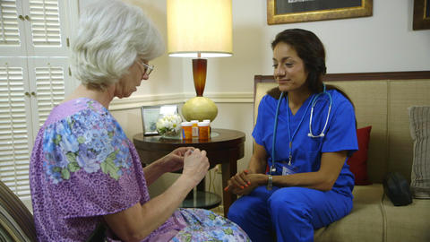 home healthcare nurse showing her elderly patient the pill box Live Action