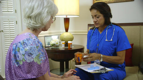 home healthcare nurse placing pills in a weekly pill box Live Action