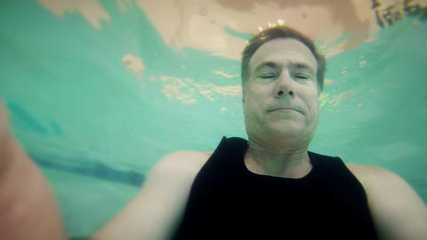 man underwater looking down at the camera Stock Video Footage