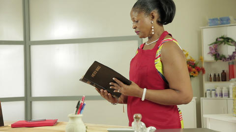 woman small business owner reads her bible Footage