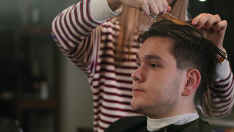 Hairdresser cutting hair with professional scissors and comb in hairdressing Archivo