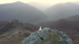 Bride in white wedding dress standing on a cliff. Aerial drone 4k movie Archivo