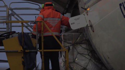 An airport worker on the elevator watching the load delivery Footage