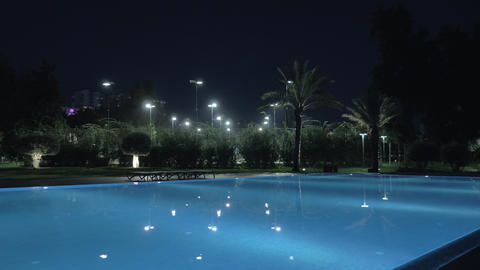 A steadicam shot of an illuminated open pool at night Live Action