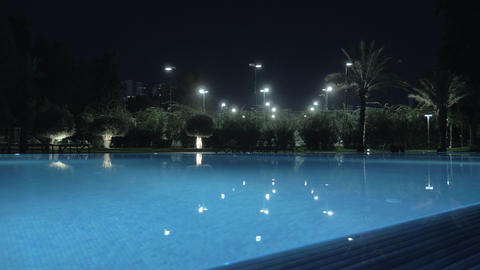 A steadicam shot of a glossy open pool surface in night illumination Live Action