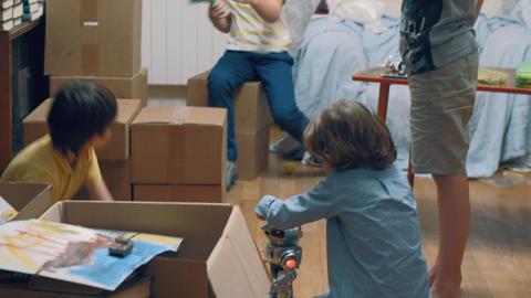 Group of kids playing among boxes GIF