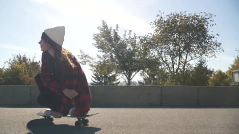 Young girl in a white hat and a plaid shirt rides a skateboard outdoors. Hipster Live Action